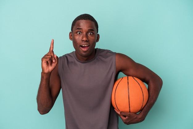 아이디어, 영감 개념을 가지고 파란색 배경에 고립 농구를 하는 젊은 아프리카계 미국인 남자.