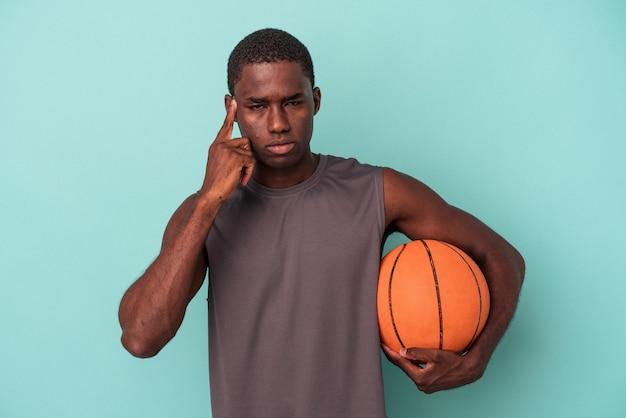 파란색 배경에 격리된 농구를 하는 젊은 아프리카계 미국인 남자가 손가락으로 사원을 가리키며 생각하고 작업에 집중했습니다.