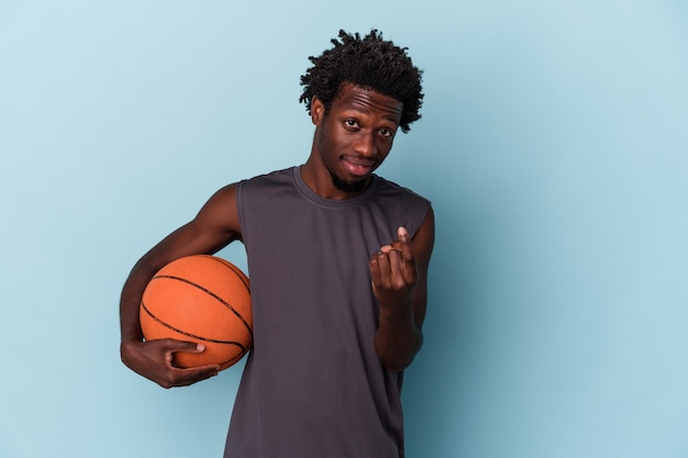 파란색 배경에 격리된 농구를 하는 젊은 아프리카계 미국인 남자가 마치 가까이 오는 것처럼 손가락으로 당신을 가리키고 있습니다.