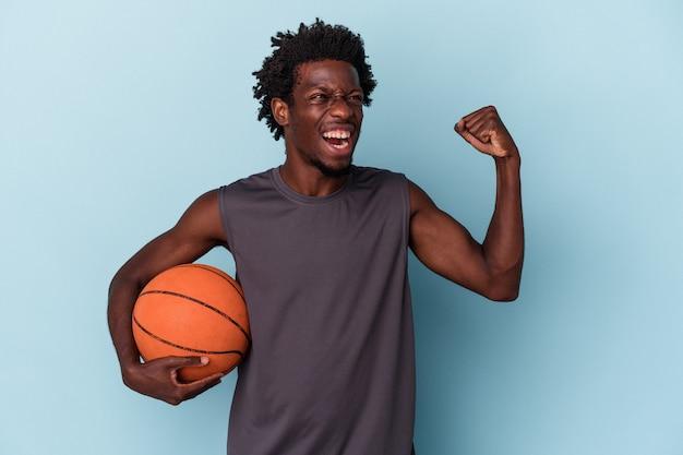 파란색 배경에 격리된 농구를 하는 젊은 아프리카계 미국인 남자가 승리, 승자 개념으로 주먹을 들고 있습니다.