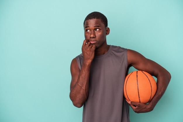 파란색 배경에 격리된 농구를 하는 젊은 아프리카계 미국인 남자는 복사 공간을 보고 있는 무언가에 대해 편안하게 생각했습니다.