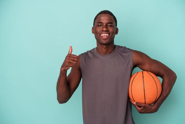 파란색 배경에 격리된 농구를 하는 젊은 아프리카계 미국인 남자가 웃고 엄지손가락을 들어올립니다.