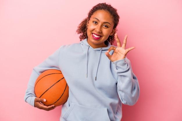 분홍색 배경에 격리된 농구를 하는 젊은 아프리카계 미국인 남자는 쾌활하고 자신감 있는 확인 제스처를 보여줍니다.