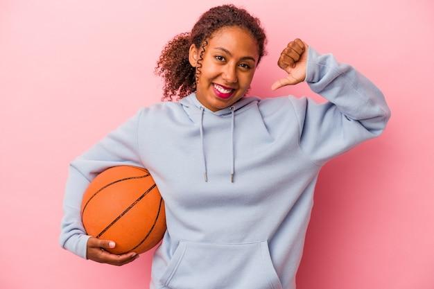 분홍색 배경에서 격리된 농구를 하는 젊은 아프리카계 미국인 남자는 자랑스럽고 자신감을 느낍니다.