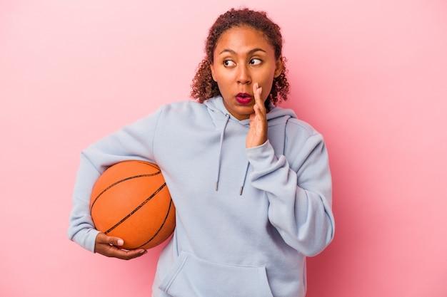 분홍색 배경에서 고립된 농구를 하는 젊은 아프리카계 미국인 남자가 비밀 핫 브레이크 뉴스를 말하고 옆을 바라보고 있다