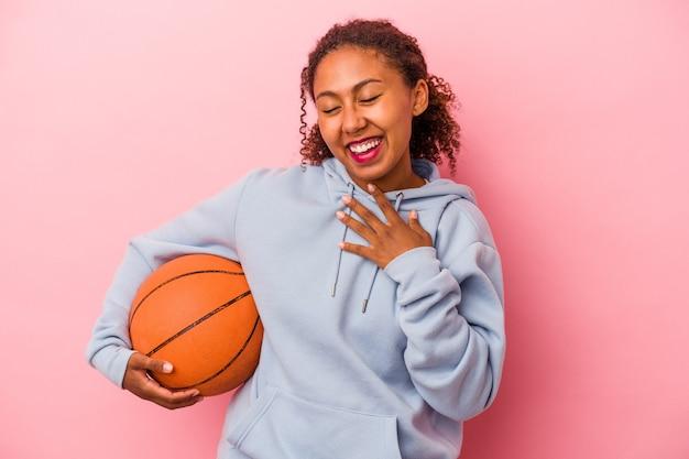 분홍색 배경에 격리된 농구를 하는 젊은 아프리카계 미국인 남자는 가슴에 손을 대고 큰 소리로 웃습니다.