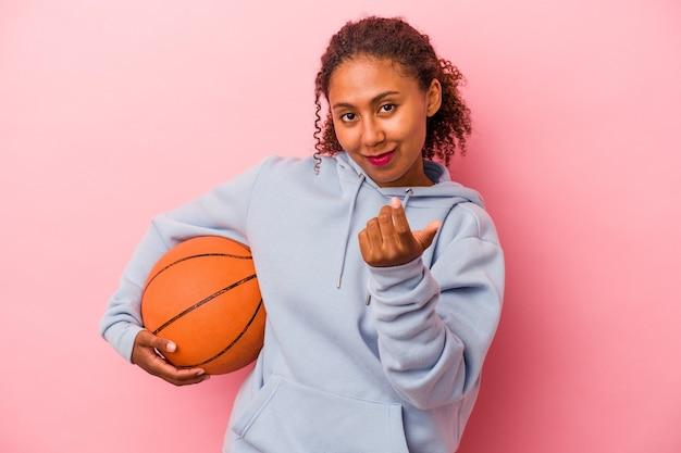 분홍색 배경에 격리된 농구를 하는 젊은 아프리카계 미국인 남자가 마치 가까이 오는 것처럼 손가락으로 당신을 가리키고 있습니다.