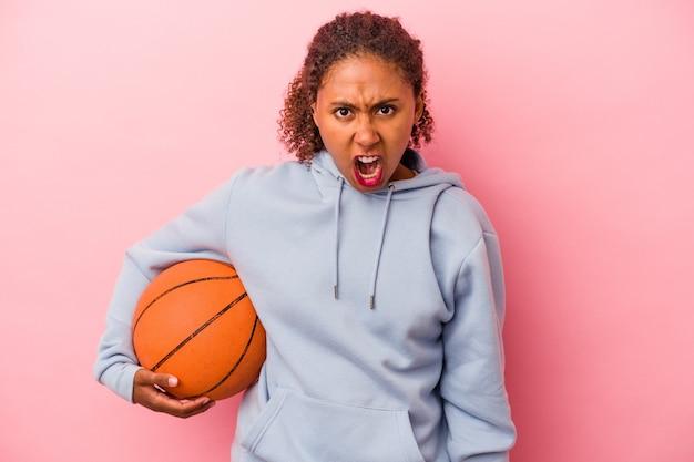 분홍색 배경에 격리된 농구를 하는 젊은 아프리카계 미국인 남자는 매우 화나고 공격적으로 비명을 지르고 있습니다.