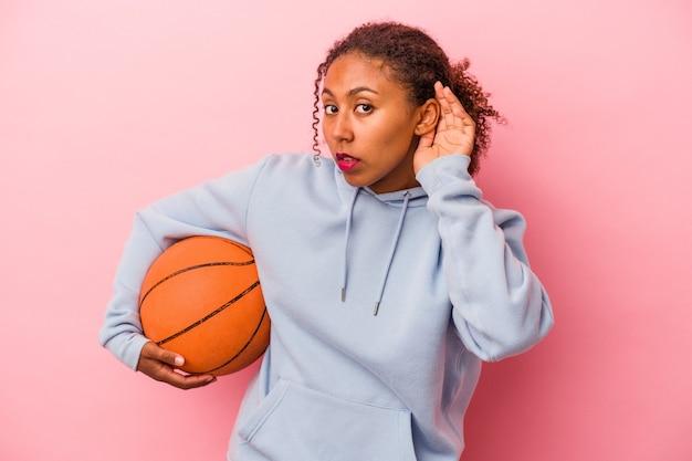 분홍색 배경에서 격리된 농구를 하는 젊은 아프리카계 미국인 남자가 가십을 들으려고 노력합니다.
