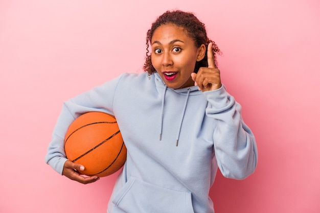 Young african american man playing basketball isolated on pink background having an idea, inspiration concept.