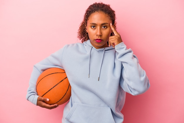 Young african american man playing basketball isolated on pink background pointing temple with finger, thinking, focused on a task.