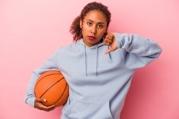 Young african american man playing basketball isolated on pink background showing a dislike gesture, thumbs down. disagreement concept.