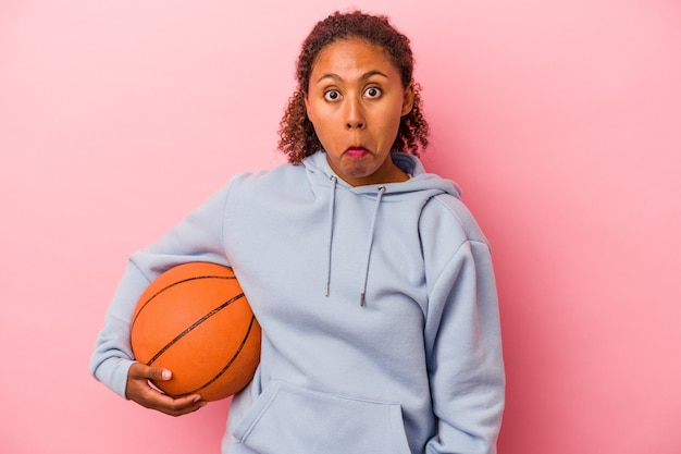 Young african american man playing basketball isolated on pink background shrugs shoulders and open eyes confused.