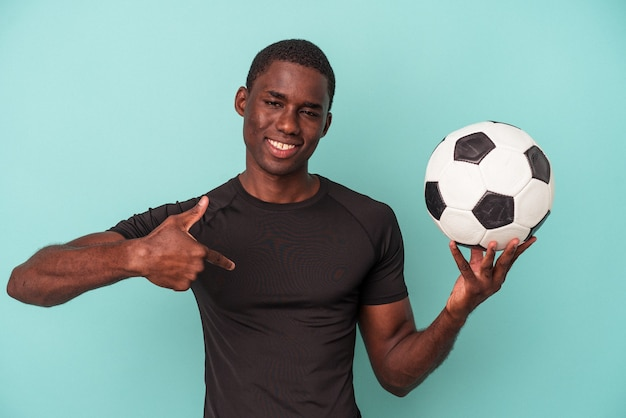 Young african american man playing football isolated on blue background person pointing by hand to a shirt copy space, proud and confident