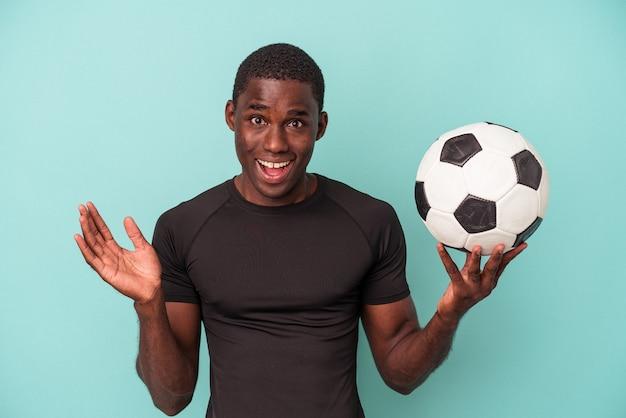 青い背景で隔離のサッカーをしている若いアフリカ系アメリカ人の男は驚いてショックを受けました。