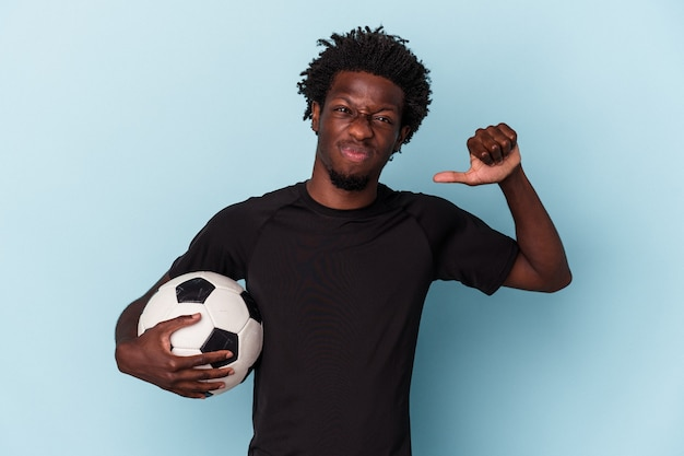 Young african american man playing soccer isolated on blue background feels proud and self confident, example to follow.