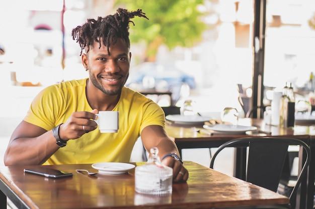 コーヒーショップで一杯のコーヒーを飲みながらリラックスしている若いアフリカ系アメリカ人の男。アーバンコンセプト。