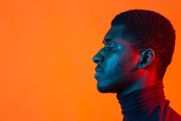 Young african-american man's listening to music in headphones in neon light. male portrait.