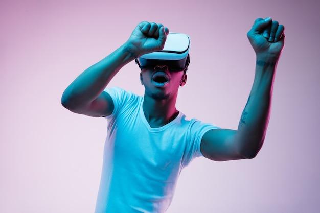 Молодой афро-американский мужчина играет и использует очки vr в неоновом свете на градиентном фоне