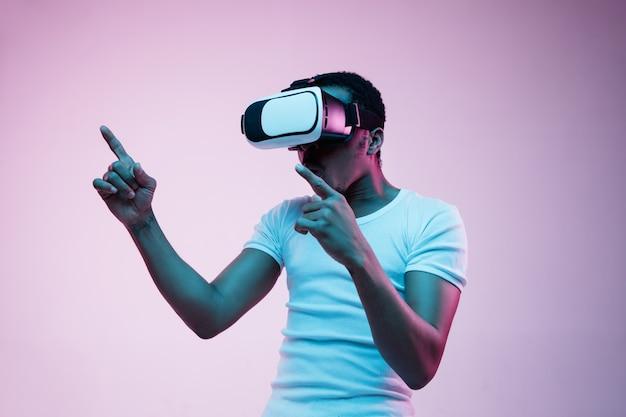 グラデーションでネオン光のvrメガネで遊んでいる若いアフリカ系アメリカ人の男