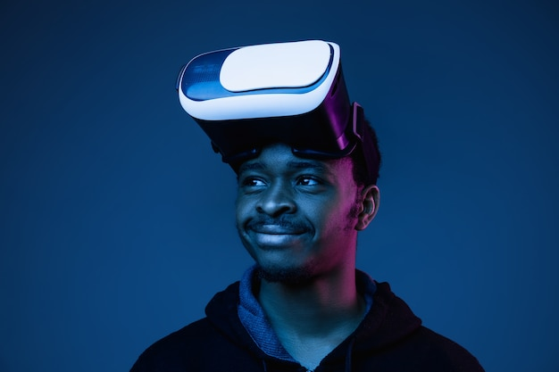 젊은 아프리카 계 미국인 남자가 그라디언트에 네온 불빛에 vr 안경을 쓰고 있습니다.