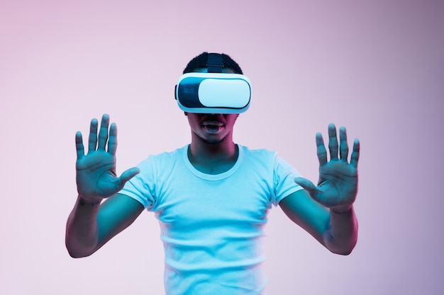 Young african-american man's playing and using vr-glasses in neon light on gradient background