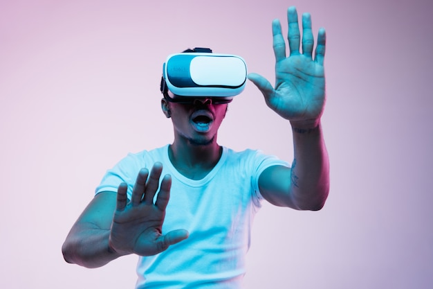 Young african-american man's playing and using vr-glasses in neon light on gradient