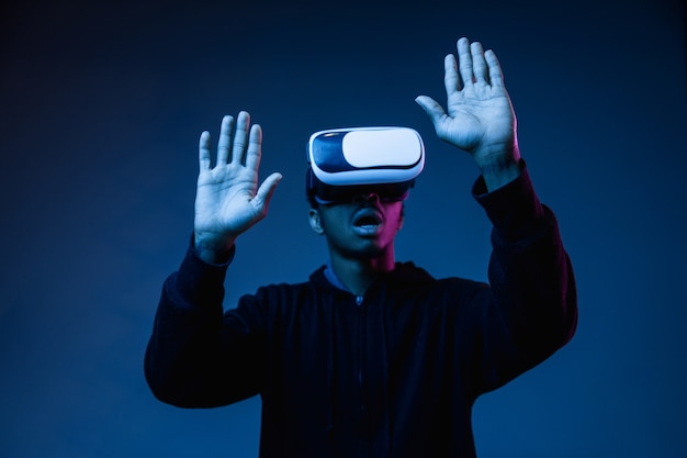 Young african-american man's playing in vr-glasses in neon light on blue