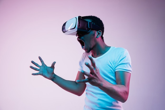Young african-american man's playing in vr-glasses in neon light on gradient background. male portrait