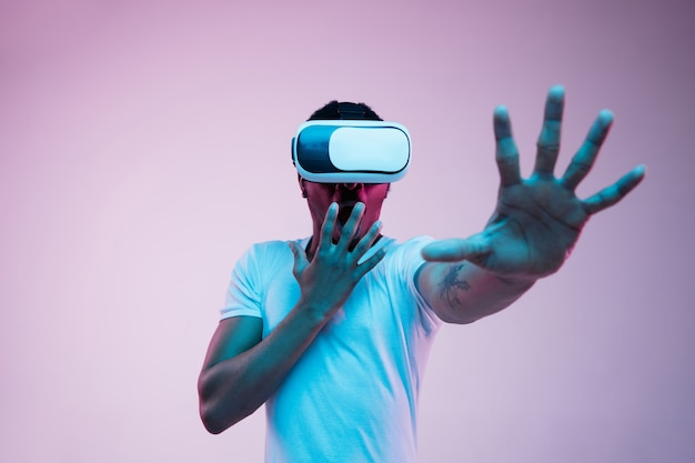 Young african-american man's playing in vr-glasses in neon light on gradient.