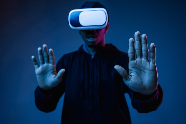 Young african-american man's playing in vr-glasses in neon light on gradient