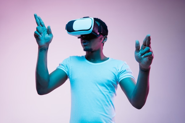 Young african-american man's pointing and using vr-glasses in neon light on gradient background. male portrait. concept of human emotions, facial expression, modern gadgets and technologies.