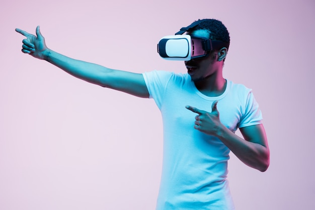 Young african-american man's pointing and using vr-glasses in neon light on gradient