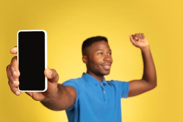 黄色のスタジオの背景、顔の表情に分離された若いアフリカ系アメリカ人の男の肖像画。コピースペースを持つ美しい男性の半分の長さの肖像画。