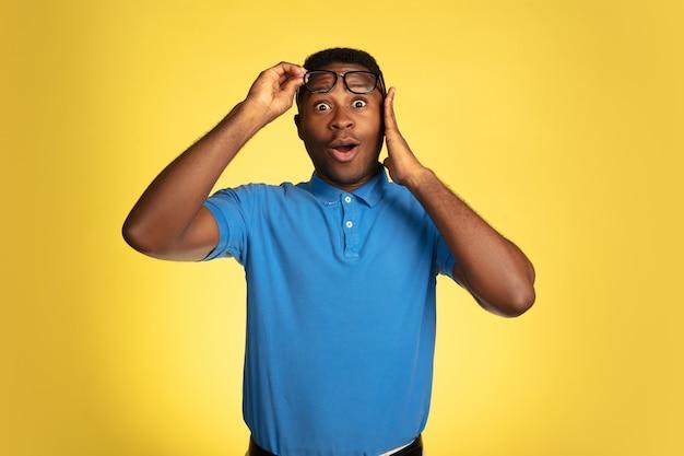 黄色のスタジオの背景、顔の表情に分離された若いアフリカ系アメリカ人の男の肖像画。