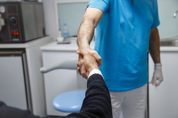 Young african-american man shaking hand of dentist having visit in medical clinic.