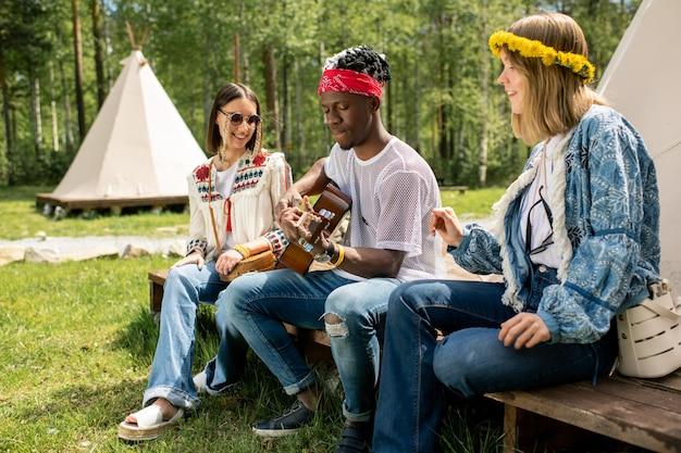 Молодой афроамериканец сидит среди красивых девушек и играет на гитаре в лесном лагере, фестивальная вечеринка
