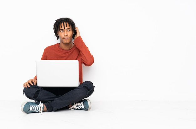 Young african american man sitting on the floor and working with his laptop having doubts