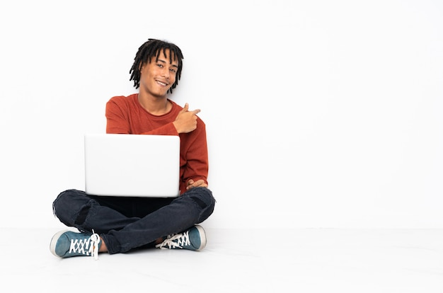 Young african american man sitting on the floor and working with his laptop pointing back
