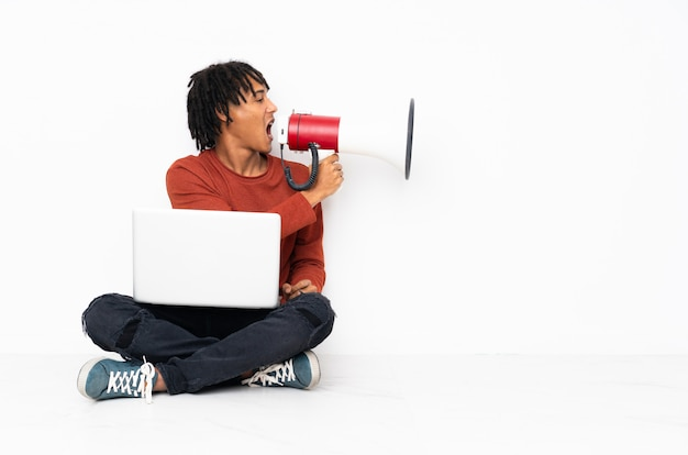Young african american man sitting on the floor and working with his laptop shouting through a megaphone