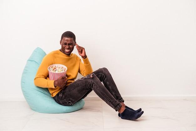 手で耳を覆う白い背景で隔離のポップコーンを食べるパフに座っている若いアフリカ系アメリカ人の男。