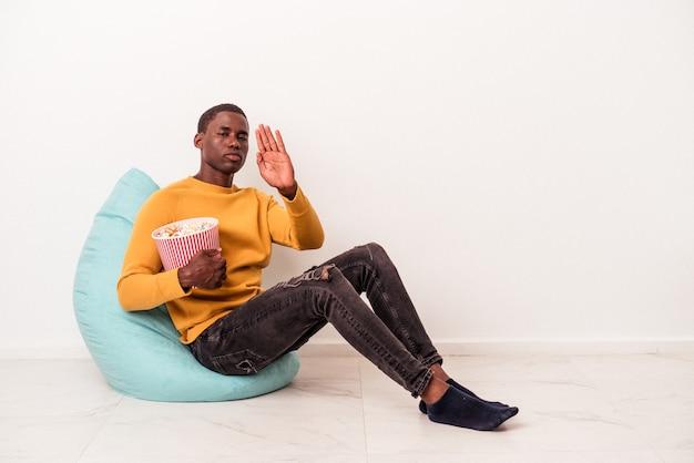 白い背景で隔離のポップコーンを食べてパフに座っている若いアフリカ系アメリカ人の男は、一時停止の標識を示している手を伸ばして立って、あなたを防ぎます。