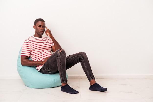 Молодой афро-американский человек, сидящий на затяжке, изолированные на белом фоне, указывая висок пальцем, думая, сосредоточился на задаче.