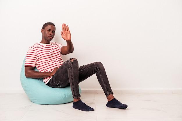 白い背景で隔離のパフに座っている若いアフリカ系アメリカ人の男性は、一時停止の標識を示している手を伸ばして立って、あなたを妨げています。