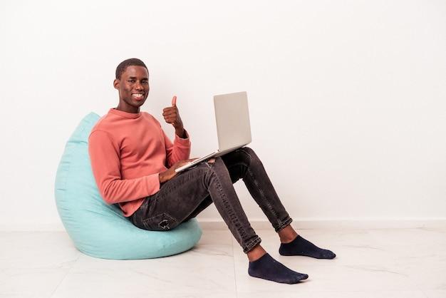 笑顔と親指を上げて白い背景で隔離のラップトップを使用してパフに座っている若いアフリカ系アメリカ人の男
