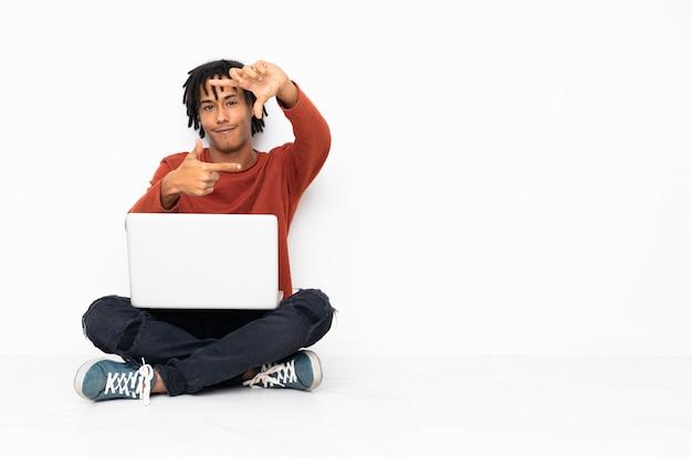床に座って、彼のラップトップの焦点を合わせている顔を使って働く若いアフリカ系アメリカ人。フレーミングシンボル
