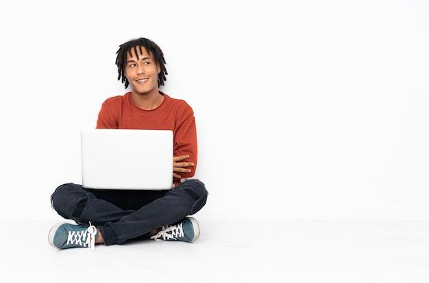 젊은 아프리카 계 미국인 남자가 바닥에 앉아 팔을 넘어 자신의 노트북을 사용하는 행복