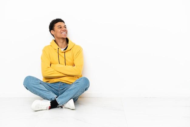 Молодой афро-американский мужчина сидит на полу, изолированном на белом фоне, счастливым и улыбающимся