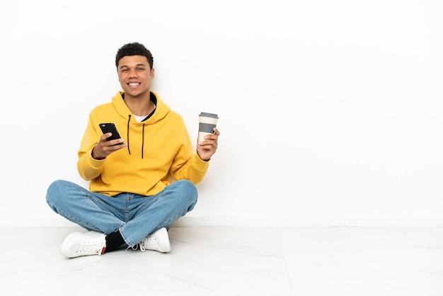 Молодой афро-американский мужчина сидит на полу, изолированном на белом фоне, держит кофе на вынос и мобильный