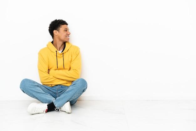 横の位置で白い背景で隔離の床に座っている若いアフリカ系アメリカ人の男